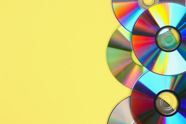 Stapels van oude en vuile cd's, dvd op pastel achtergrond. gebruikte en stoffige schijf met exemplaarruimte Premium Foto