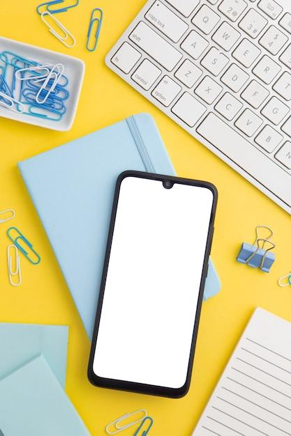 Stationaire samenstelling op gele achtergrond met telefoon Gratis Foto