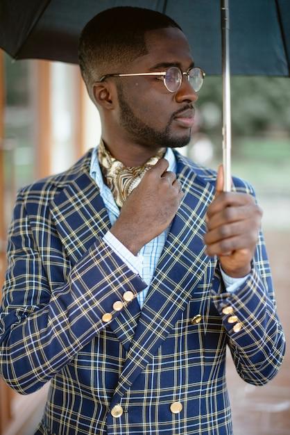 Stedelijk portret van knappe afro-amerikaanse zakenman permanent in het centrum van de stad bij bewolkt weer onder zwarte paraplu gekleed in formele kleding. Premium Foto