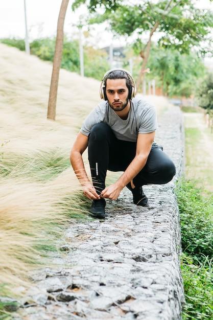 Stedelijke atleet die zijn schoenen vastmaakt Gratis Foto