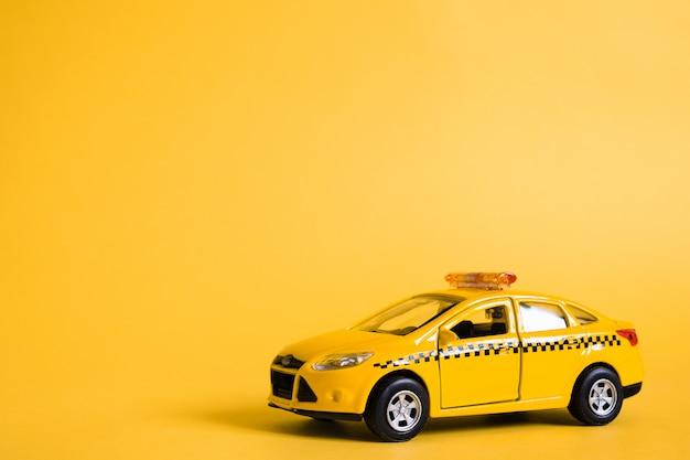 Stedelijke taxi en bezorgservice concept. speelgoed gele taxi automodel Premium Foto