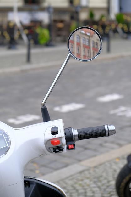 Stedelijke witte scooter wordt geparkeerd op geplaveide weg in een toeristisch centrum van de stad Premium Foto