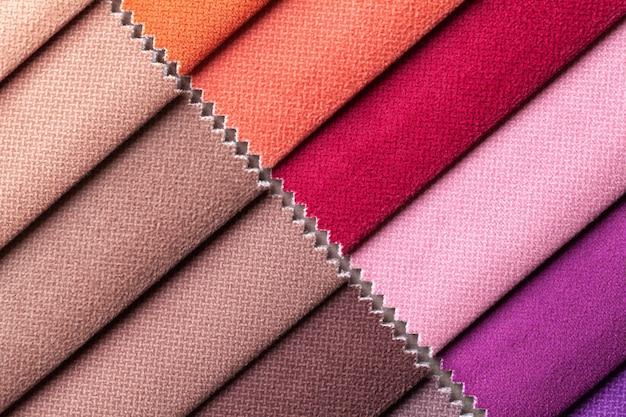 Steekproef van fluweel textiel verschillende kleuren, achtergrond. catalogus en palettoon van interieurstof voor meubels, close-up. verzameling van veelkleurige doek. Premium Foto