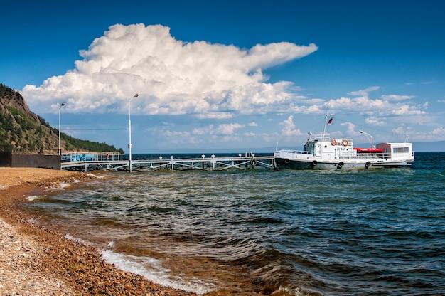 Steenachtige kust en schip op de pier in zonnige dag en cloud Premium Foto