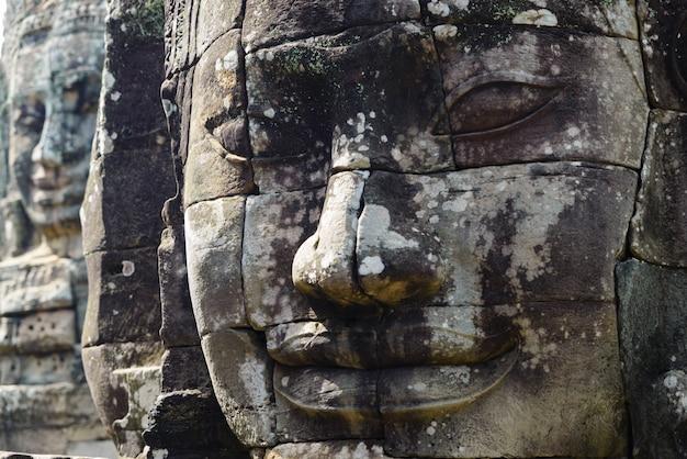 Steengezichten in bayon, de tempel van angkor thom, het selectieve licht van de nadrukzonsondergang. boeddhisme meditatie concept, wereldberoemde reisbestemming, cambodja toerisme. Premium Foto