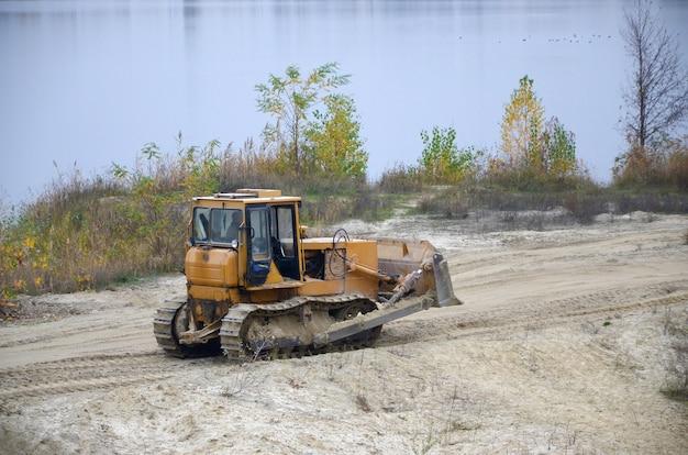 Steengroeveaggregaat met zware machines. caterpillar lader graafmachine met backhoe rijden naar bouwplaats steengroeve Premium Foto
