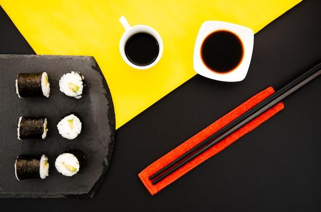 Steenplaat met sushibroodjes en kom met sojasaus op een zwarte achtergrond met eetstokjes Gratis Foto