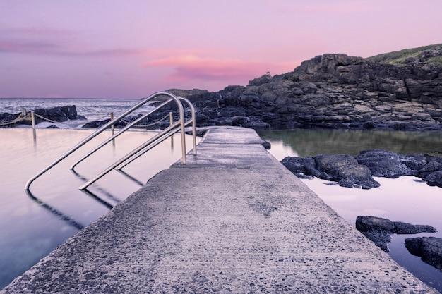 Steenweg in de watervorming bij de kust tijdens zonsondergang Gratis Foto