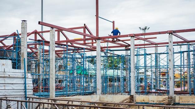 Steiger op huis, renovatie met vervagen bouwvakkers op een steiger en materiaal op grond, Premium Foto