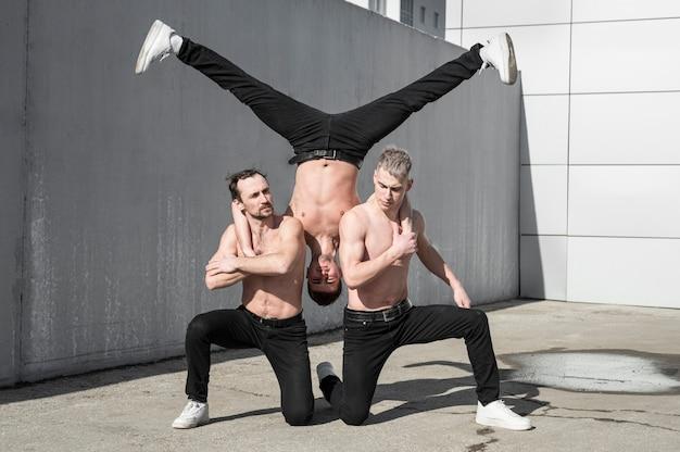 Stel buiten drie shirtloze hiphopdansers Gratis Foto