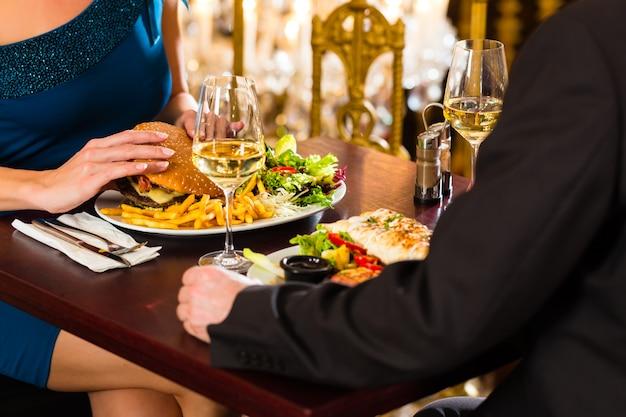 Stel, man en vrouw een fine dining restaurant ze eten fastfood, hamburger en friet Premium Foto