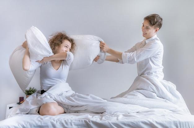 Stellen gebruiken een kussen om elkaar op het bed te plagen. Premium Foto