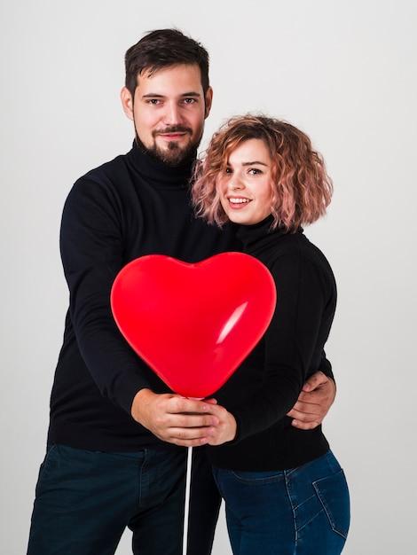 Stellend paar met ballon voor valentijnskaarten Gratis Foto