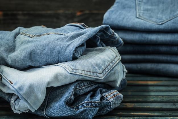 Stelletje jeans op houten achtergrond, modieuze kleding Gratis Foto