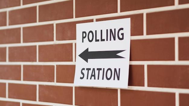 Stembureauteken met richting op bakstenen muur Gratis Foto