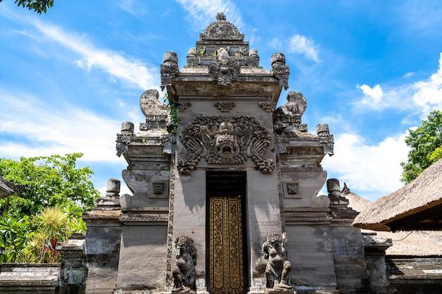 Stenen ingang naar een hindoe-tempel met een houten deur Premium Foto
