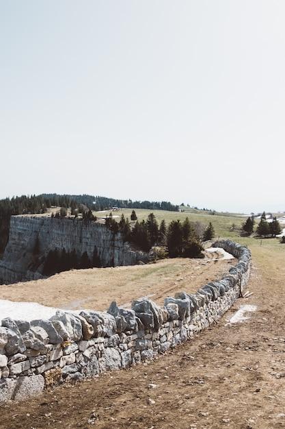 Stenen muur in de buurt van een klif op een groen veld onder een bewolkte hemel Gratis Foto