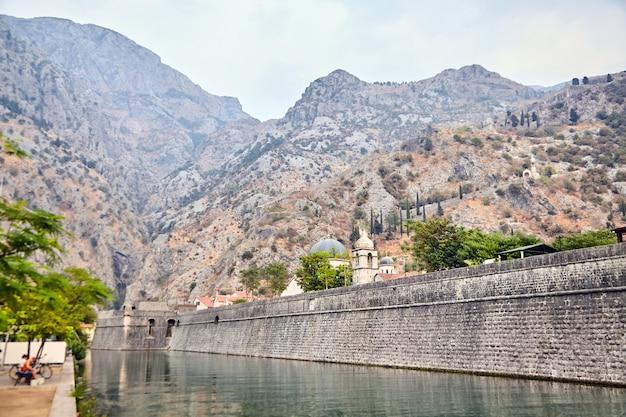 Stenen muur van oude vesting van kotor, montenegro. kerk en bergen op de achtergrond Premium Foto