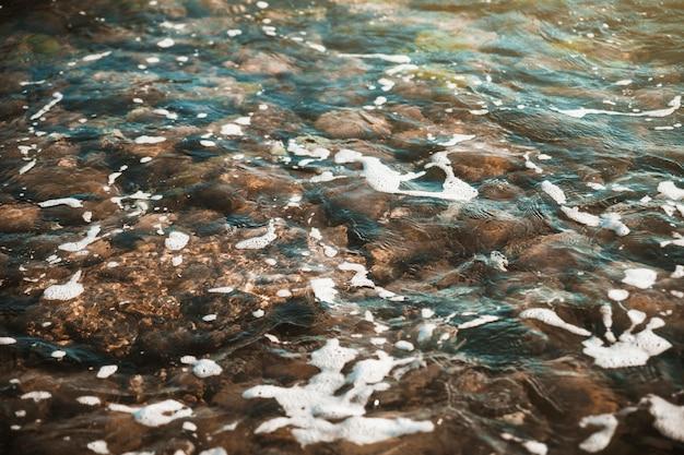 Stenen onder water zwaaien Gratis Foto