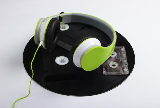 Stereohoofdtelefoons, videocassettes, vinylplaten, audiocassette op een wit oppervlak Premium Foto