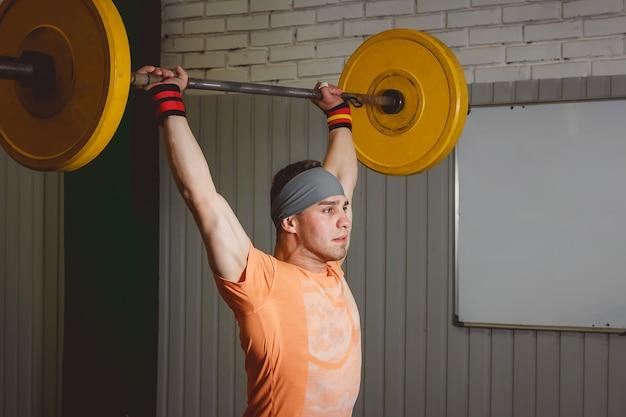 Sterk crossfit atleet in een zware overhead squat lift in een cross-fit box gym Premium Foto