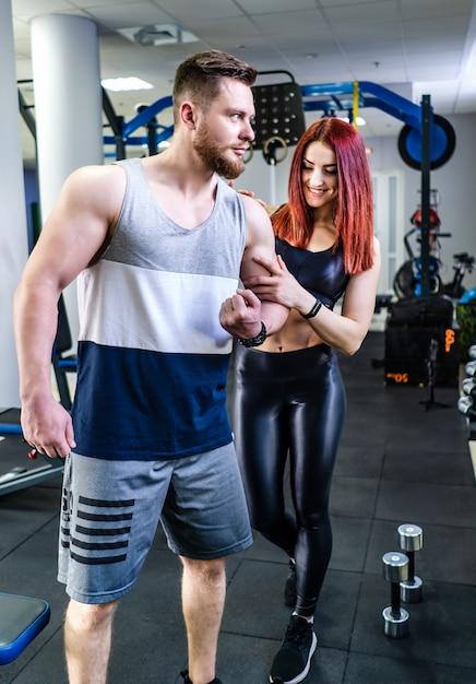 Sterke atleet toont zijn gespierde lichaam aan de mooie vrouw in gezondheidsclub. het glimlachende meisje raakt de bicepsen van het mannetje op de krommingsarm Premium Foto