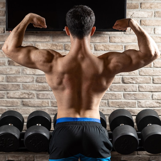 Sterke atletische man fitness model poseren rugspieren, triceps op sportschool Premium Foto