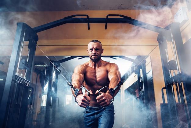 Sterke bodybuilder die oefeningen doet in de sportschool Premium Foto