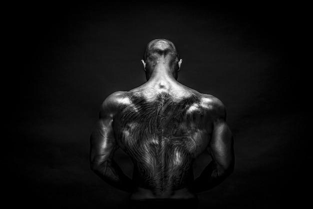 Sterke bodybuilder die zich voordeed en spieren toont Premium Foto