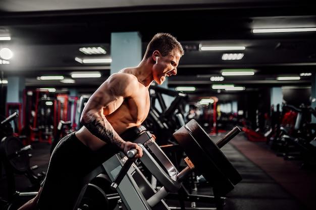 Sterke bodybuilder die zwaargewicht oefening voor terug op machine doet. t-pull oefening Premium Foto