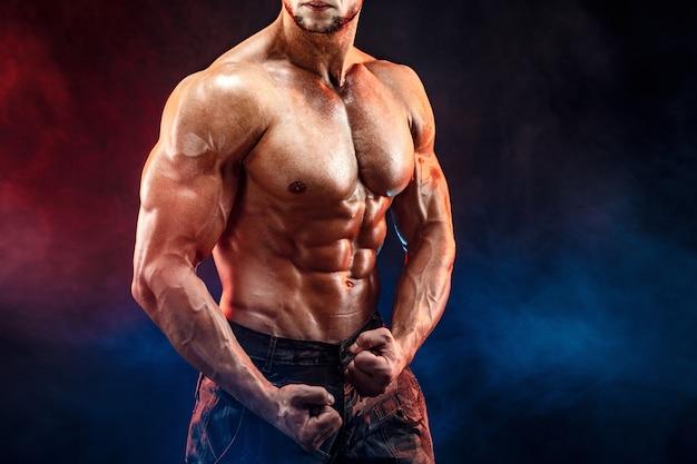 Sterke bodybuilder man in militaire broek met perfecte buikspieren, schouders, biceps, triceps, borst Premium Foto