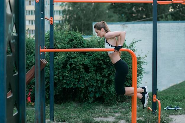 Sterke en fysiek geschikte jonge vrouw die tricepsonderdompelingen op parallelle staven doen bij park. Gratis Foto