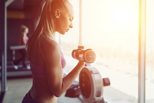 Sterke en mooie atletische vrouw training in de sportschool Gratis Foto