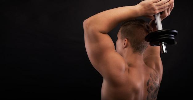 Sterke man maakt oefeningen op triceps. gespierd lichaam met vrije ruimte voor fitnessartikelen. close-up shot training handen. twee-armige triceps-extensie Gratis Foto