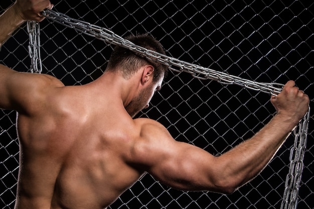 Sterke man op hek met kettingen Gratis Foto
