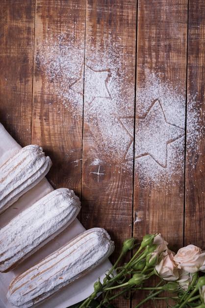 Stervorm getrokken op houten bureau met gebakken eclairs en rozen Gratis Foto