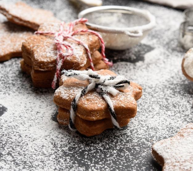 Stervormige gebakken peperkoekkoekjes bestrooid met poedersuiker op een zwarte tafel, close-up Premium Foto