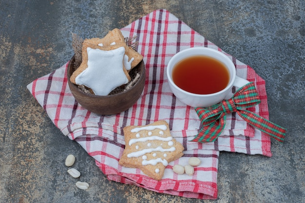 Stervormige peperkoekkoekjes en kopje thee op tafellaken. hoge kwaliteit foto Gratis Foto