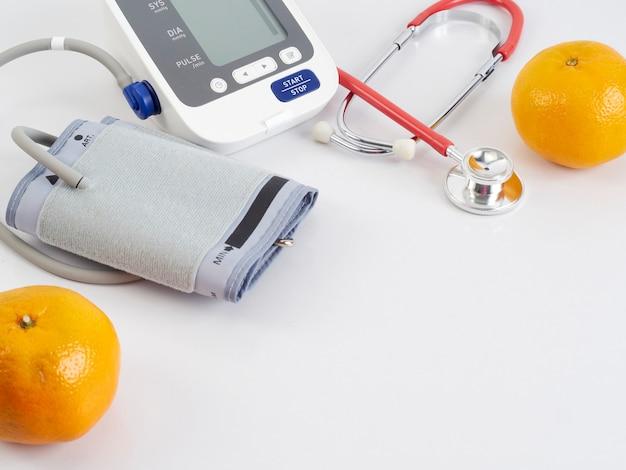 Stethoscoop en automatische bloeddrukmeter met sinaasappels Premium Foto