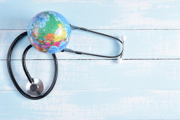Stethoscoop en globe op blauwe en witte pastel houten achtergrond. gezondheidszorg en medisch concept. Premium Foto