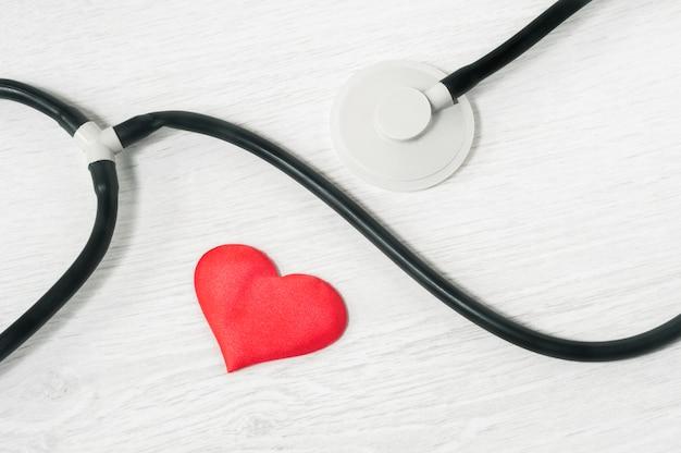 Stethoscoop en hart op een lichte achtergrond bovenaanzicht. gezondheidszorg concept Premium Foto