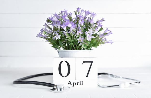 Stethoscoop en purpere bloemen in een pot met kalender van het de tekst de houten blok van april 7 Premium Foto