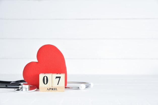Stethoscoop en rood hart met 7 april tekst houten blokkalender op witte houten achtergrond. Premium Foto