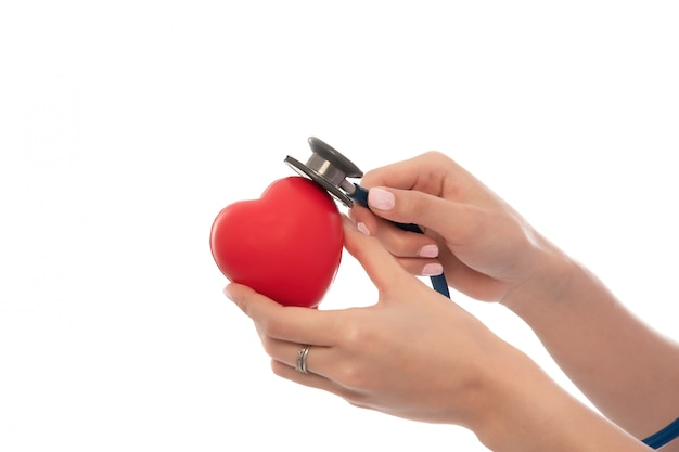 Stethoscoop met hart in artsenhanden op wit close-up, copyspace, gezondheidszorg worden geïsoleerd die. Premium Foto