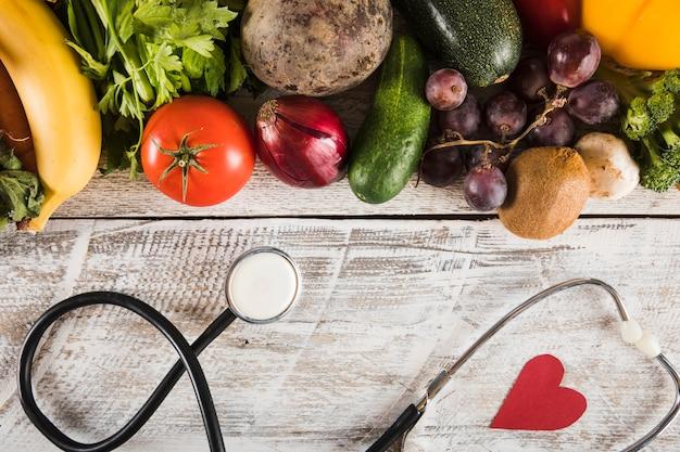 Stethoscoop met hartvorm dichtbij verse groenten op houten achtergrond Gratis Foto