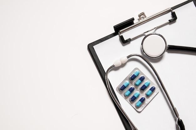Stethoscoop met pillen van medicijnen op medisch klembord, medisch concept. concept gezondheidszorg. Gratis Foto
