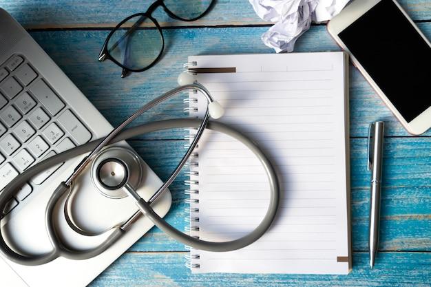 Stethoscoop op laptop op tafel. object voor arts en technologie Premium Foto