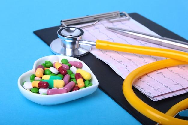 Stethoscoop, recept en kleurrijke assortiment pillen en capsules op plaat. Premium Foto