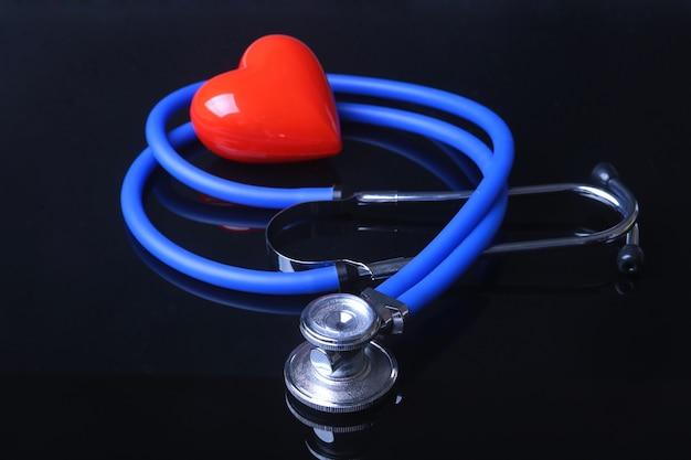 Stethoscoop, rode hart en bloeddrukmeter op zwarte spiegelachtergrond. Premium Foto