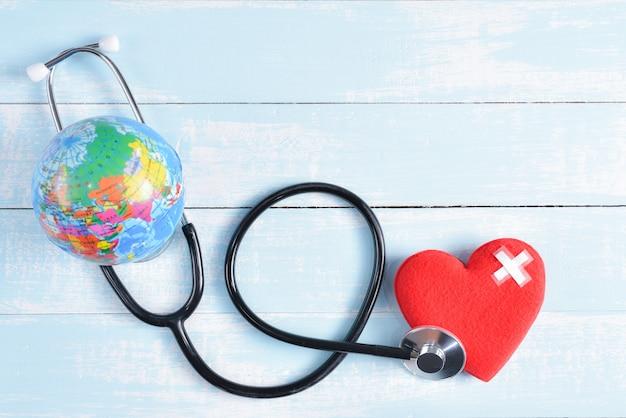 Stethoscoop, rood hart en globe op blauwe en witte pastel houten achtergrond. Premium Foto